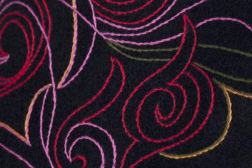 Detaljer av stort brodert jakkemønster i rosalill farger