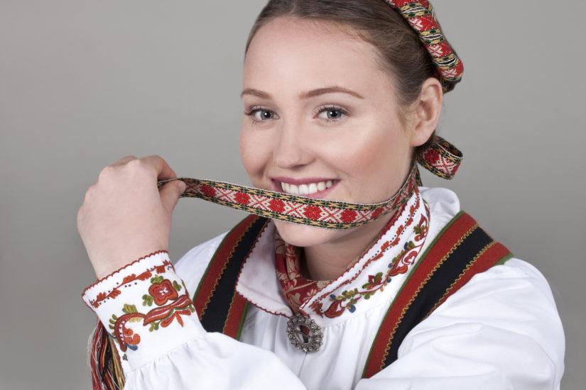 Blid jente med Vest-Telemarksbunad med svart-jakke