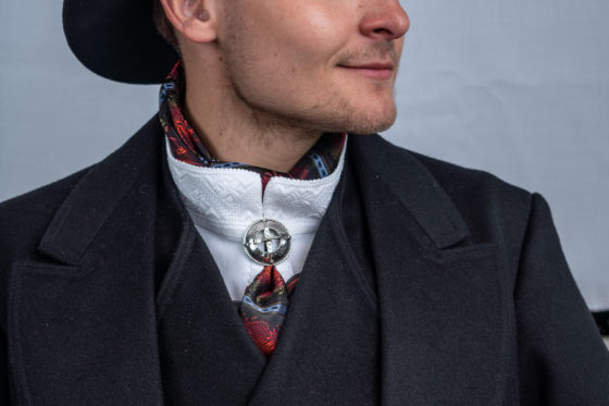 Sort herrebunad med hvit skjorte og hatt