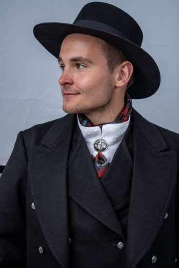 Sort herrebunad med silketørkle i halsen og hatt på hodet.